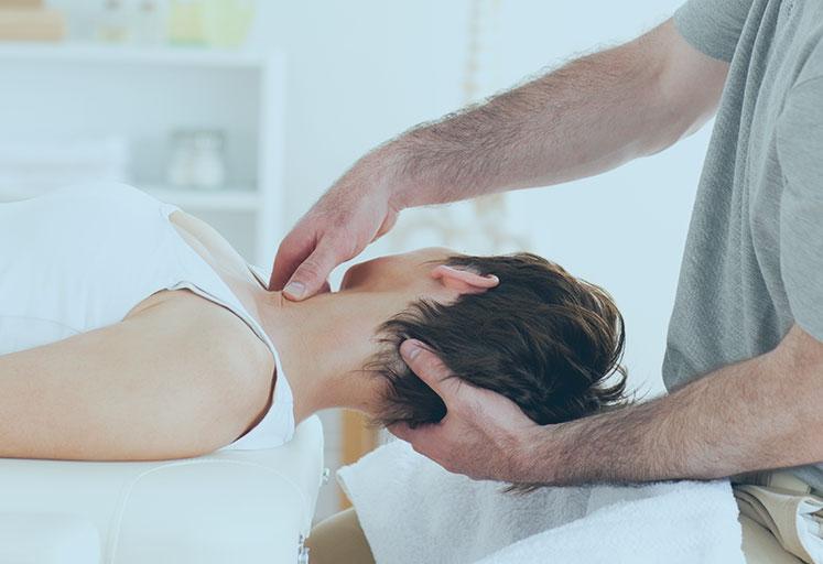 Chiropractor Massaging A Womans Neck